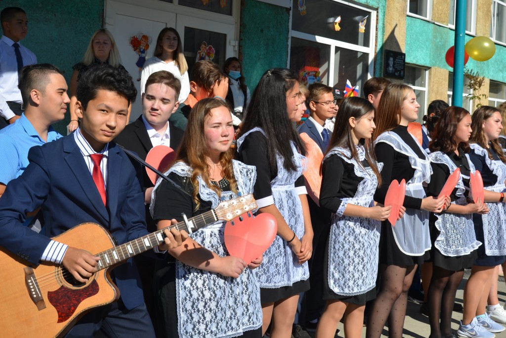 Олег Борин (слева в первом ряду) и его одноклассники исполняют песню в честь начала учебного года